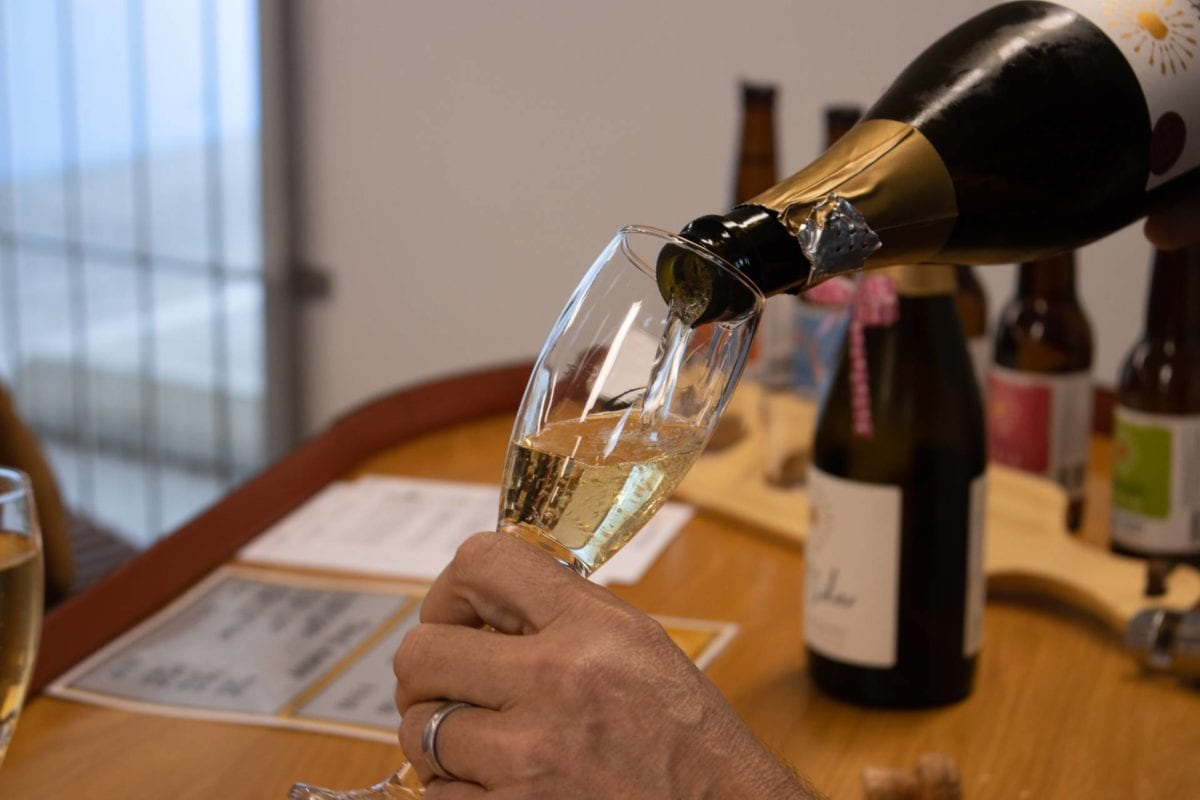 Pouring Brut+ Cider into champagne glass, Cellar Door